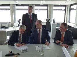 (v.l.: OB Klaus Weichel, Geschäftsführer Philipp P. Gross, Notar Martin Naumann; hinten: Bernd Oberländer, Niederlassungsleiter Kaiserslautern)