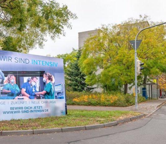 """Plakat der neuen Personalgewinnungskampagne """"Wir sind intensiv"""" vor dem Verwaltungsgebäude des Universitätsklinikums. (Foto: Universitätsklinikum Heidelberg)"""