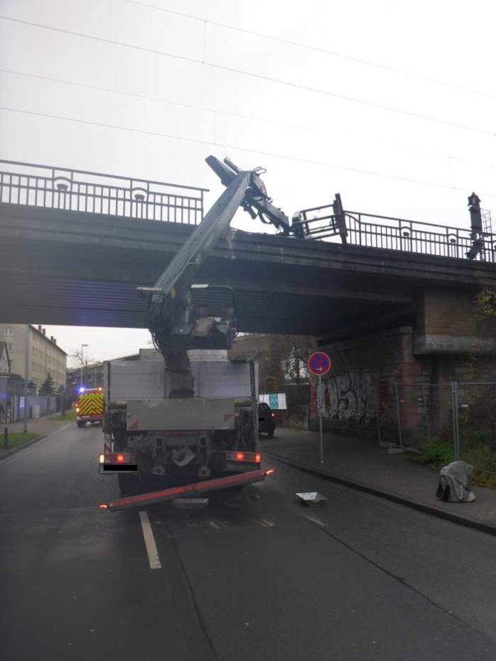 LKW bleibt mit Ladekran an Bahnüberführung hängen