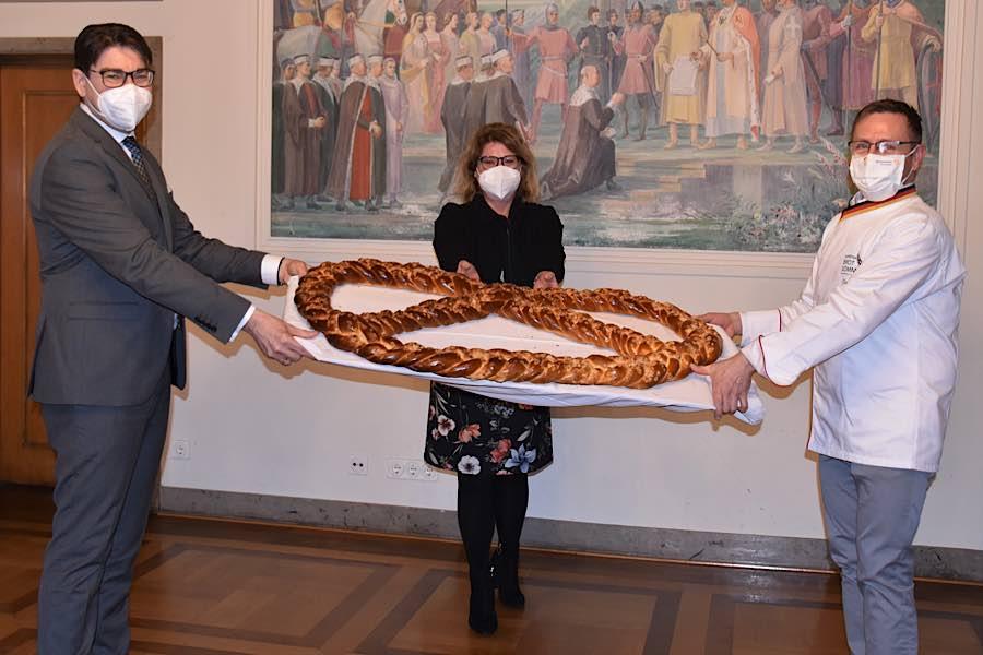 Bäckermeister Becker (r.) überreichte Landaus OB Hirsch auch in diesem Jahr eine riesige Neujahrsbrezel als Glücksbringer. Gleichstellungsbeauftragte Evi Julier brachte die Brezel anschließend ins Frauenhaus. (Quelle: Stadt Landau)